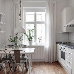 Idéer för att renovera ett minimalistiskt linjärt kök och matrum, med luckor med upphöjd panel, vita skåp, mellanmörkt trägolv, brunt golv, vitt stänkskydd, stänkskydd i tunnelbanekakel och vita vitvaror