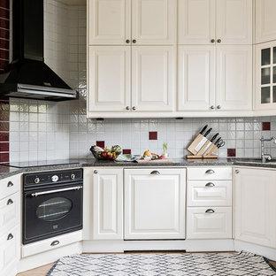 Idéer för att renovera ett mellanstort minimalistiskt u-kök, med vita skåp, granitbänkskiva, flerfärgad stänkskydd, svarta vitvaror och luckor med upphöjd panel
