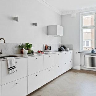Idéer för ett skandinaviskt linjärt kök, med vita skåp, marmorbänkskiva, vitt stänkskydd och stänkskydd i marmor