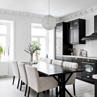 Inredning av ett minimalistiskt stort grå grått kök, med svarta skåp, integrerade vitvaror, skåp i shakerstil, vitt stänkskydd, stänkskydd i tunnelbanekakel och beiget golv