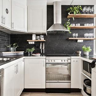 Idéer för minimalistiska svart u-kök, med en dubbel diskho, luckor med infälld panel, vita skåp, svart stänkskydd, rostfria vitvaror, ljust trägolv, en halv köksö och beiget golv