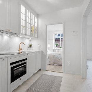 Inspiration för ett mellanstort minimalistiskt linjärt kök, med en undermonterad diskho, luckor med upphöjd panel, vita skåp, grått stänkskydd, stänkskydd i sten, svarta vitvaror, ljust trägolv och marmorbänkskiva
