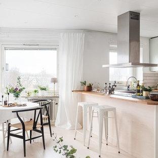 Idéer för att renovera ett skandinaviskt kök, med släta luckor, gröna skåp, träbänkskiva, vitt stänkskydd, svarta vitvaror, målat trägolv, en halv köksö och vitt golv