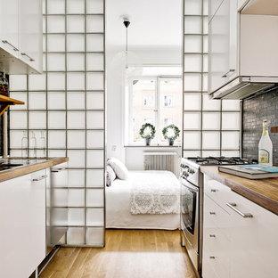 Idéer för skandinaviska parallellkök, med släta luckor, vita skåp, träbänkskiva, grått stänkskydd, rostfria vitvaror och mellanmörkt trägolv