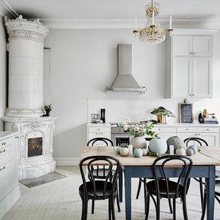 Modelo de cocina lineal, clásica, grande, con armarios con paneles empotrados, puertas de armario grises, salpicadero blanco, electrodomésticos de acero inoxidable, suelo de madera pintada y encimera de mármol