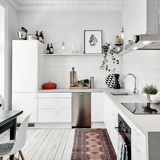 Design ideas for a mid-sized transitional l-shaped kitchen in Gothenburg with a single-bowl sink, flat-panel cabinets, white cabinets, concrete benchtops, stainless steel appliances, painted wood floors and no island.