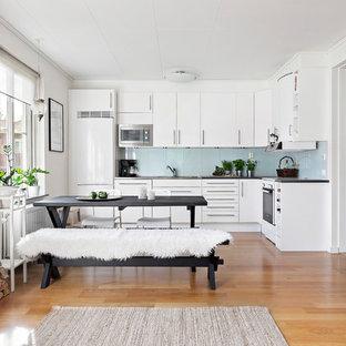 Idéer för att renovera ett stort skandinaviskt kök, med släta luckor, vita skåp, mellanmörkt trägolv, blått stänkskydd, glaspanel som stänkskydd och vita vitvaror