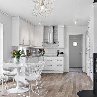 Skandinavisk inredning av ett litet kök, med släta luckor, vita skåp, stänkskydd i tunnelbanekakel, grått stänkskydd, integrerade vitvaror, mellanmörkt trägolv och beiget golv