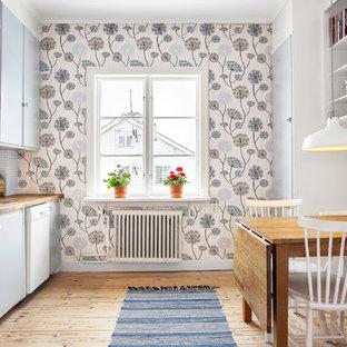 Idéer för att renovera ett mellanstort nordiskt linjärt kök och matrum, med en nedsänkt diskho, släta luckor, grå skåp, träbänkskiva, vitt stänkskydd, rostfria vitvaror och ljust trägolv