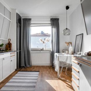 Inspiration för små skandinaviska grått kök, med en dubbel diskho, släta luckor, grå skåp, rostfria vitvaror och brunt golv