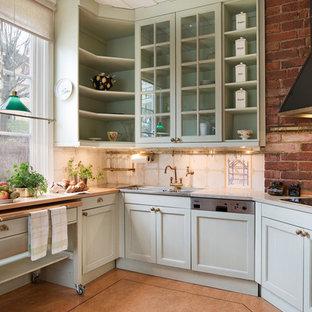 Lantlig inredning av ett avskilt, mellanstort linjärt kök, med en dubbel diskho, luckor med glaspanel, gröna skåp och marmorbänkskiva