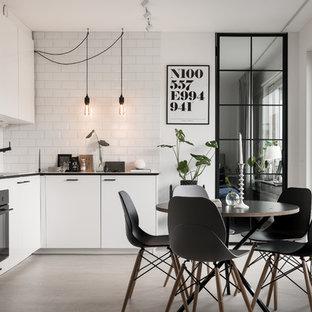 Foto på ett mellanstort nordiskt l-kök, med släta luckor, vita skåp, integrerade vitvaror, betonggolv och vitt golv