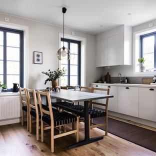 Idéer för ett stort minimalistiskt linjärt kök och matrum, med släta luckor, vita skåp, ljust trägolv och beiget golv