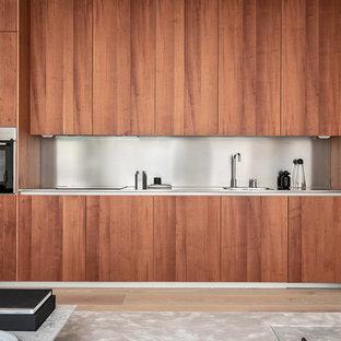 Foto på ett stort funkis linjärt kök med öppen planlösning, med en enkel diskho, släta luckor, skåp i mellenmörkt trä, bänkskiva i rostfritt stål, rostfria vitvaror och ljust trägolv