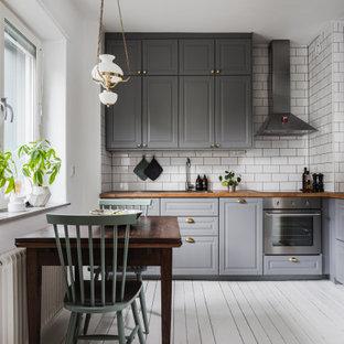 Inspiration för ett vintage brun brunt kök och matrum, med en nedsänkt diskho, luckor med upphöjd panel, grå skåp, träbänkskiva, vitt stänkskydd, stänkskydd i tunnelbanekakel, rostfria vitvaror och vitt golv