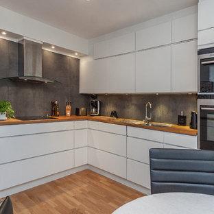 Foto på ett funkis kök, med en dubbel diskho, släta luckor, vita skåp, träbänkskiva, svart stänkskydd, rostfria vitvaror och ljust trägolv