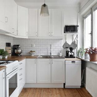 Idéer för att renovera ett nordiskt l-kök, med en dubbel diskho, skåp i shakerstil, vita skåp, träbänkskiva, vitt stänkskydd, stänkskydd i tunnelbanekakel, vita vitvaror och ljust trägolv