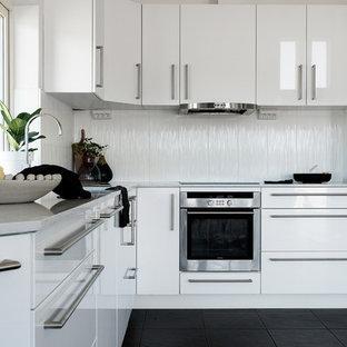 Foto på ett mellanstort nordiskt grå l-kök, med vita skåp, marmorbänkskiva, vitt stänkskydd, svart golv, släta luckor och rostfria vitvaror