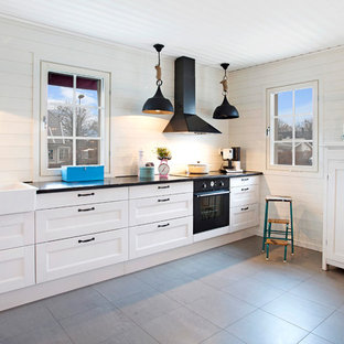 Foto på ett stort minimalistiskt linjärt kök, med en rustik diskho, luckor med infälld panel, vita skåp, vitt stänkskydd och svarta vitvaror