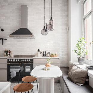 Inspiration för skandinaviska vitt kök, med släta luckor, grå skåp, vitt stänkskydd, svarta vitvaror och grått golv