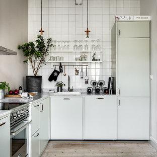 Inspiration för ett nordiskt l-kök, med släta luckor, gröna skåp, marmorbänkskiva, ljust trägolv, en nedsänkt diskho, vitt stänkskydd, rostfria vitvaror och beiget golv