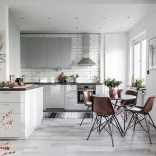 Inredning av ett minimalistiskt mellanstort kök med öppen planlösning, med släta luckor, grå skåp, granitbänkskiva, vitt stänkskydd, stänkskydd i tunnelbanekakel, rostfria vitvaror och grått golv