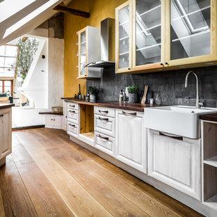 Idéer för att renovera ett avskilt, mellanstort medelhavsstil parallellkök, med luckor med glaspanel, svart stänkskydd, stänkskydd i skiffer och rostfria vitvaror