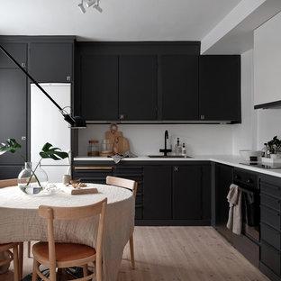 Foto på ett minimalistiskt kök, med en nedsänkt diskho, laminatbänkskiva, vitt stänkskydd, ljust trägolv, släta luckor, svarta skåp, svarta vitvaror och beiget golv