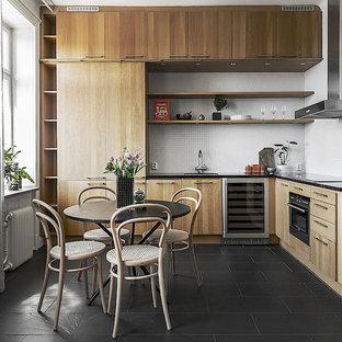 Idéer för mellanstora minimalistiska svart kök, med släta luckor, skåp i ljust trä, en undermonterad diskho, vitt stänkskydd, svarta vitvaror och svart golv