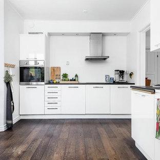 Bild på ett skandinaviskt l-kök, med släta luckor, vita skåp, rostfria vitvaror och mörkt trägolv