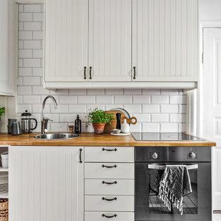 Inspiration för ett nordiskt beige linjärt beige kök, med vita skåp, träbänkskiva, vitt stänkskydd, rostfria vitvaror, en nedsänkt diskho, luckor med lamellpanel och stänkskydd i tunnelbanekakel
