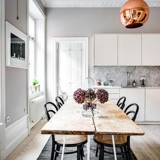Idéer för mellanstora minimalistiska linjära kök och matrum, med en undermonterad diskho, släta luckor, vita skåp, grått stänkskydd, stänkskydd i sten, svarta vitvaror och ljust trägolv