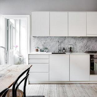 Exempel på ett nordiskt linjärt kök, med en enkel diskho, vita skåp, marmorbänkskiva, stänkskydd i marmor, vita vitvaror och ljust trägolv
