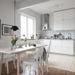 Idéer för små minimalistiska linjära kök och matrum, med släta luckor, vita skåp, bänkskiva i rostfritt stål, vitt stänkskydd, rostfria vitvaror, ljust trägolv och beiget golv