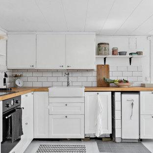 Idéer för ett mellanstort minimalistiskt beige l-kök, med en rustik diskho, luckor med infälld panel, vita skåp, träbänkskiva, vitt stänkskydd, stänkskydd i tunnelbanekakel, svarta vitvaror och grått golv