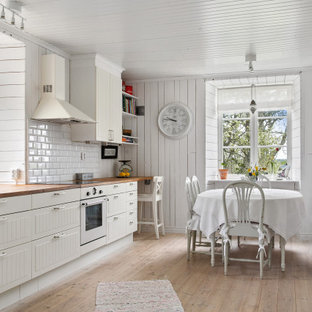 Inspiration for a mid-sized country single-wall eat-in kitchen in Other with a farmhouse sink, louvered cabinets, white cabinets, wood benchtops, white splashback, subway tile splashback, white appliances, light hardwood floors, no island, beige floor and beige benchtop.