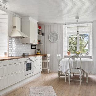 Inspiration för mellanstora lantliga linjära beige kök och matrum, med en rustik diskho, vita skåp, träbänkskiva, vitt stänkskydd, stänkskydd i tunnelbanekakel, vita vitvaror, ljust trägolv, beiget golv och släta luckor