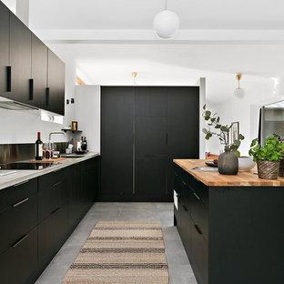 Idéer för ett skandinaviskt l-kök, med släta luckor, svarta skåp, träbänkskiva, integrerade vitvaror, en köksö och grått golv