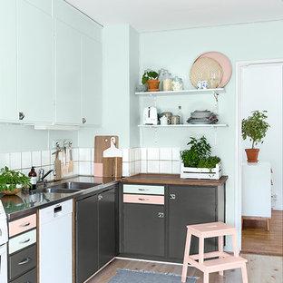 Nordisk inredning av ett litet l-kök, med en dubbel diskho, grå skåp, vitt stänkskydd, vita vitvaror och ljust trägolv