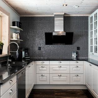 Bild på ett minimalistiskt svart svart u-kök, med en dubbel diskho, luckor med upphöjd panel, vita skåp, svart stänkskydd, stänkskydd i mosaik, rostfria vitvaror och brunt golv