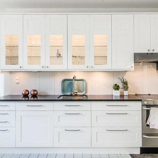 Inspiration för stora minimalistiska linjära kök, med en undermonterad diskho, skåp i shakerstil, vita skåp, vitt stänkskydd, rostfria vitvaror och målat trägolv