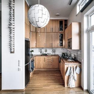 Inspiration för ett minimalistiskt brun brunt u-kök, med en nedsänkt diskho, släta luckor, skåp i mellenmörkt trä, träbänkskiva, vitt stänkskydd, rostfria vitvaror, mellanmörkt trägolv och brunt golv