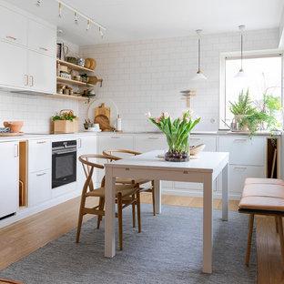 Skandinavisk inredning av ett mellanstort kök, med släta luckor, vita skåp, bänkskiva i kvarts, vitt stänkskydd, stänkskydd i tunnelbanekakel, svarta vitvaror, ljust trägolv och brunt golv