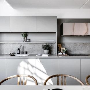 Idéer för att renovera ett skandinaviskt grå linjärt grått kök och matrum, med en undermonterad diskho, släta luckor, grå skåp, grått stänkskydd och svarta vitvaror