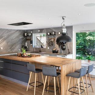 Exempel på ett stort industriellt beige beige l-kök, med släta luckor, grå skåp, träbänkskiva, mellanmörkt trägolv, en köksö, beiget golv, en enkel diskho, grått stänkskydd och stänkskydd i sten