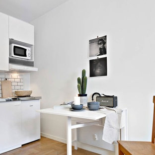 Small scandinavian kitchen pictures - Small danish medium tone wood floor kitchen photo in Other with flat-panel cabinets, white cabinets, white backsplash, subway tile backsplash, white appliances and no island