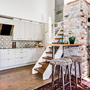 Inredning av ett lantligt stort linjärt kök och matrum, med en nedsänkt diskho, luckor med lamellpanel, beige skåp, bänkskiva i rostfritt stål, flerfärgad stänkskydd, mellanmörkt trägolv och en halv köksö