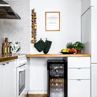 Foto på ett minimalistiskt kök, med släta luckor, skåp i mellenmörkt trä, vitt stänkskydd, mörkt trägolv och brunt golv