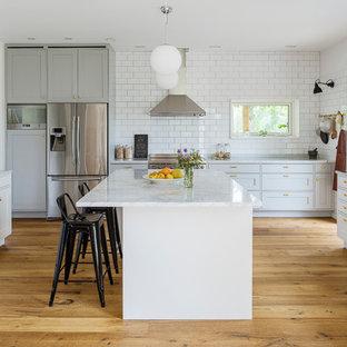 Exempel på ett stort klassiskt kök och matrum, med en dubbel diskho, skåp i shakerstil, marmorbänkskiva, rostfria vitvaror, en köksö, vita skåp, vitt stänkskydd, stänkskydd i tunnelbanekakel och ljust trägolv