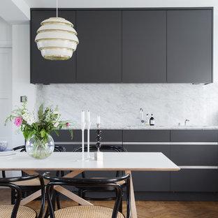 Bild på ett mellanstort minimalistiskt linjärt kök och matrum, med släta luckor, svarta skåp, vitt stänkskydd, stänkskydd i sten, mellanmörkt trägolv och marmorbänkskiva